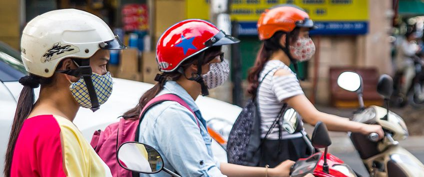 Women driving two-wheelers with masks